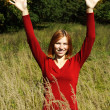 Young girl in red shirt standing on field in tall grass, smiling — Stock Photo