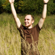 Young man standing on field in tall grass, smiling and raising h — Stock Photo #14510235