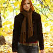 Young redhead girl in warm clothes looking at camera, autumn tre — Stock Photo