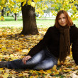 Young redhead girl in warm clothes sitting near autumn tree and — Stock Photo