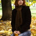 Рыжая молодая девушка в теплой одежде сидит возле Осеннее дерево и — Стоковое фото