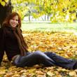 jonge roodharige meisje in warme kleren zitten in de buurt van herfst boom, smi — Stockfoto