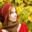 Portrait of young redhead girl in warm autumn dress outdoor — Stock Photo