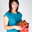 Young brunette girl opening a gift, smiling and looking at camer — Stock Photo