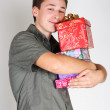 Young happy brunette man holding many gifts and smiling — Stock Photo