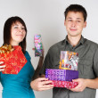 Young happy brunette man and girl holding many gifts and smiling - Stock Photo