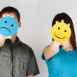 Man and woman holding paper cards with sad and fun smiles — Stock Photo
