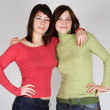 Two young brunette girls in red and green shirts embracing — Stock Photo #14512085