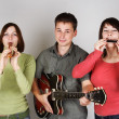 Band of two young women and man playing on flute, harp and guita — Stock Photo