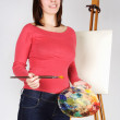 Young girl in red shirt standing near easel, holding brush and p — Stock Photo #14512129