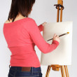 Young girl in red shirt standing near easel and painting, back v — Stock Photo