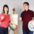 Young man and girl standing near easel, holding brushes with pal — 图库照片