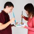 Young man and girl standing and mixing paint on palette — Stock fotografie