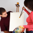Girl holding palette, painting on canvas easel, man looking on p — Stock Photo