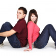 Young man and woman sitting back to back and smiling, isolated — Stock Photo
