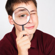 Young man holding magnifier and looking through it, big eye - Photo