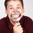 Young man holding magnifier and showing teeth through it — Stock Photo #14512195