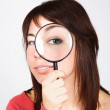 Young woman holding magnifier and looking through it, big eye — Stock Photo