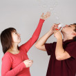 Young man blowing out soap bubbles, girl in red shirt smiling an — Stock Photo #14512213