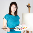 Young girl in blue shirt standing near easel, holding brush and — Stock Photo