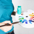 Closeup of woman in blue shirt mixing paint on palette — Stock Photo