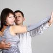 Man and woman in silver dress and gloves dancing waltz and looki - Stock Photo