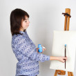 Young girl in blue shirt standing near easel and painting, blank — Stock Photo