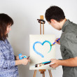 Man and girl holding brushes and palette, painting blue heart — ストック写真