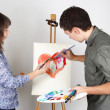 Man and girl holding brushes and palette, painting red heart — ストック写真
