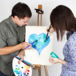 Man and girl holding brushes and palette, painting blue heart — 图库照片