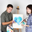 Man and girl holding brushes and palette, painting blue heart — Stock fotografie