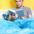 Young man lying in bed and reading book, bright interior — Stock Photo #14512835