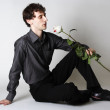Min elegant clothes sitting on floor, holding rose and lookin — Stock Photo #14513379