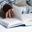 Closeup of man in sport shirt lying near opened book and turning — Stock Photo #14513441