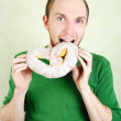 Man in green shirt biting big cracknel with white topping and lo — Stock Photo