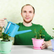 Photo: Man in green shirt sitting near table and watering plants in bri