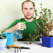 Stock Photo: Man sitting near table with gardening equipment and sprinkling c