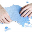 Closeup of mans hands assembling blue puzzle pieces, isolated — Stock Photo #14513905