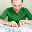 Man in green shirt assembling blue puzzle pieces — Stock Photo #14513909