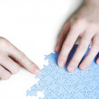Closeup of mans hands assembling blue puzzle pieces, isolated — Stock Photo #14513935