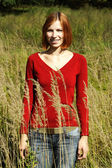 Young girl in red shirt standing on field in tall grass and smil — Stock Photo