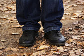 Closeup of man's legs in jeans and black boots, outdoor in autum — Stockfoto