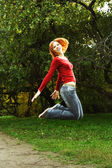 Young girl in red shirt and jeans jumping outdoor — Stockfoto