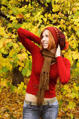 Young redhead girl in warm autumn dress standing outdoor, lookin — Stock Photo