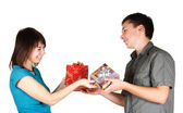 Young brunette girl and man present gifts to each other and smil — Stock Photo