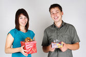 Young brunette girl and man holding gifts and smiling — Stock Photo