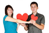 Beauty girl and man holding two paper hearts, smiling and lookin — Stock Photo
