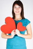 Gülümseyen ve arayan iki kağıt kalp tutan genç güzellik kız — Stok fotoğraf