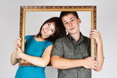 Man and woman holding gold decorative frame and standing inside — Stock Photo