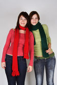 Portrait of two young girls in green and red scarfs — Stock Photo